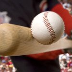 baseball player hits the ball with his bat with crowd in background