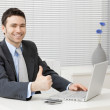 Happy young businessman showing success with thumb up at office, smiling.