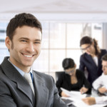 Closeup portrait of happy businessman, looking at camera, smiling. Business team working in the background, sitting at desk.